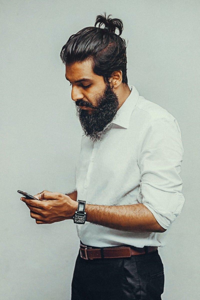 long black beard standing man in white shirt using mobile phone